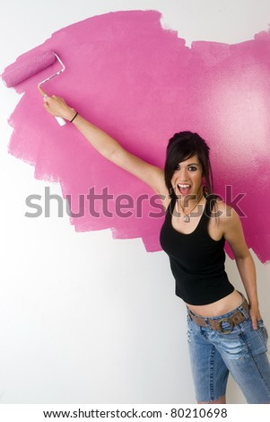 Get Pink Sexy Girl paints wall rolls on color in do it yourself project - stock photo