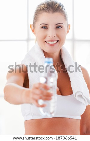 Get refreshed! Beautiful mature woman in sports clothing stretching out a bottle with water and smiling