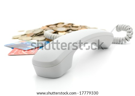 Get rich using telephone: receiver; pile of coins and credit cards - stock photo