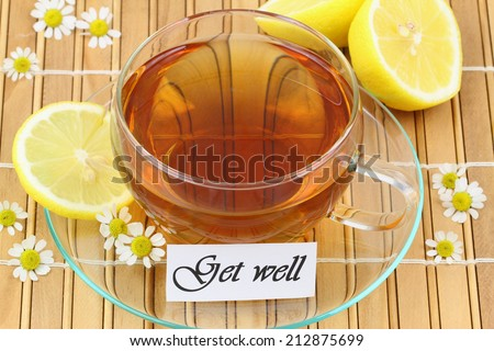 Get well card with cup of chamomile tea and lemon on bamboo mat  - stock photo