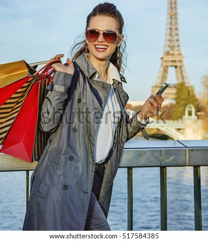 Get your bags ready for the Paris autumn sales. happy young trendy woman in sunglasses with shopping bags looking into the distance and writing sms near Eiffel tower