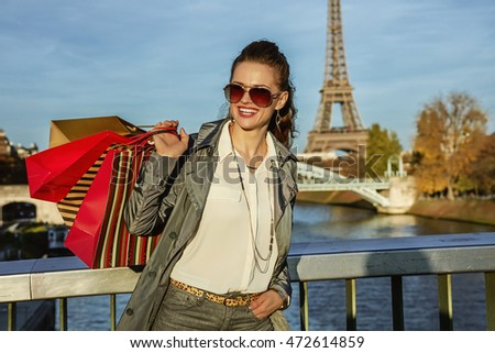 Get your bags ready for the Paris autumn sales. smiling young elegant woman in sunglasses with shopping bags looking into the distance in Paris, France