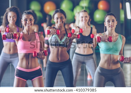 Getting fit with smile. Young beautiful women in sportswear with perfect bodies exercising with dumbbells and looking at camera with smile at gym