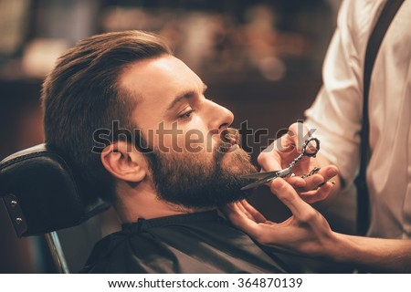 Getting perfect shape. Close-up side view of young bearded man getting beard haircut by hairdresser at barbershop - stock photo
