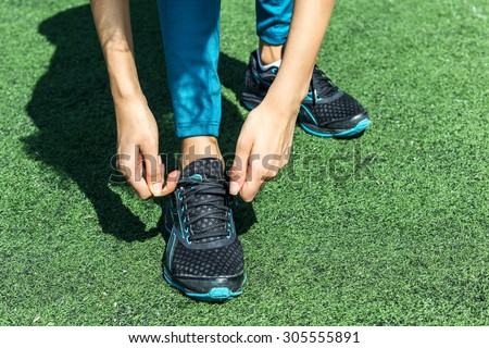 Getting ready for a run. Runner feet running on road closeup on shoe. woman fitness  jog workout . tie shoelaces