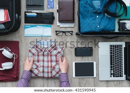 Getting ready for a trip and packing a suitcase, a man is holding his shirt before putting it into his bag, travel and vacations concept - stock photo