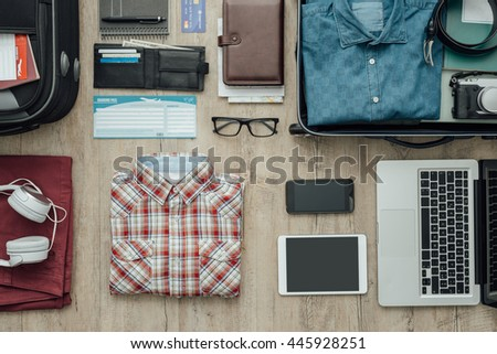 Getting ready for a trip and packing a suitcase before leaving; accessories, clothing and personal items on a desktop, travel and vacations concept