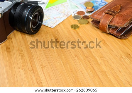 getting ready for travel, money, map and photo camera on wooden table with copy space - stock photo
