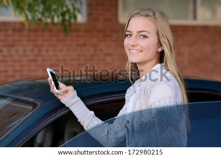 Getting Ready to Drive. Young woman getting in to a car while holding a smartphone. - stock photo