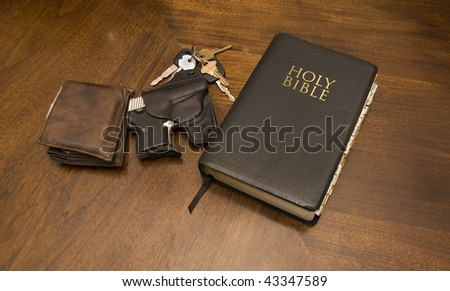 Getting ready to go to church showing a Bible, gun, keys and wallet on top of a table. - stock photo