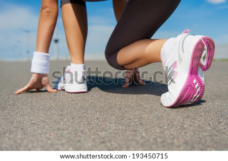 Getting ready to run.  Close-up image of woman in sports shoes standing in starting line  - stock photo