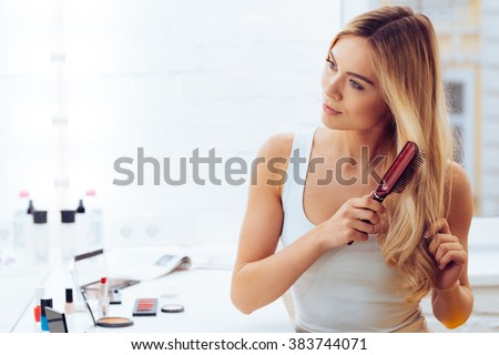 Getting rid of tangles. Beautiful young woman looking at her reflection in mirrorand brushing her long hair while sitting at the dressing table - stock photo