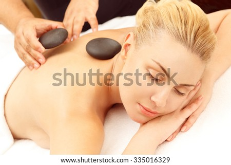 Getting stone massage. Beautiful relaxed woman getting stone therapy massage at the SPA salon  - stock photo