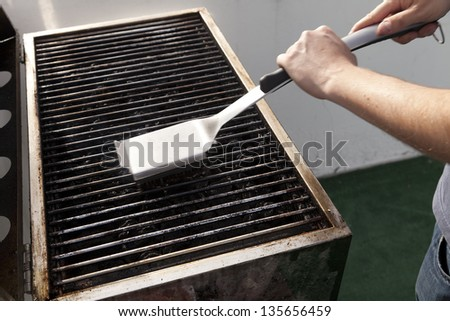Getting the grill ready for some cooking - scraping old fat with the grill brush, blurred by the swift movements of cleaning. - stock photo