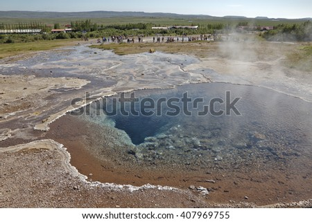 geyser in front of the landscape of iceland