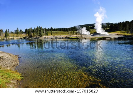 Geysers steaming near a river in Yellowstone National Park - stock photo