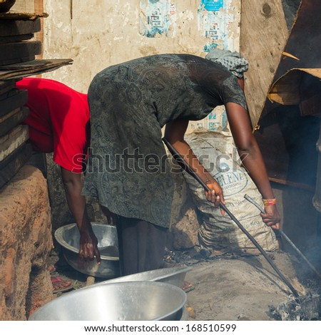 GHANA - MARCH 2, 2012: Unidentified Ghanaian cooks the fish on the market in Ghana, on March 2nd, 2012. People in Ghana suffer from poverty due to the slow development of the country