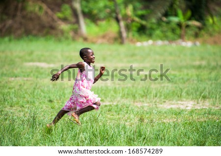 GHANA - MARCH 3, 2012: Unidentified Ghanaian girl runs happily in the field in Ghana, on March 3rd, 2012. Children in Ghana suffer from poverty due to the unstable economical situation - stock photo