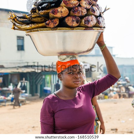 GHANA - MARCH 2, 2012: Unidentified Ghanaian woman carries the fish on her back to sell it in Ghana, on March 2nd, 2012. People in Ghana suffer from poverty due to the slow development of the country - stock photo