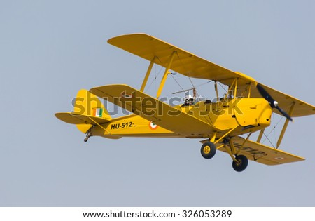 Ghaziabad, India - October 8, 2015: A Indian Air Force Tiger Moth biplane aircraft flying at 83rd Air Force Day parade. The skilled pilot did complex midair maneuvers and daring aerial feats.