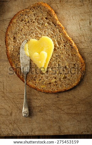 ghee or melted butter in heart shape on wholemeal bread - stock photo