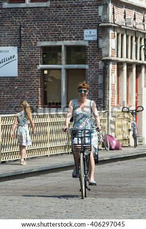 GHENT, BELGIUM - JULY 3, 2015: A smiling woman riding a bicycle on one of the streets of the city. - stock photo