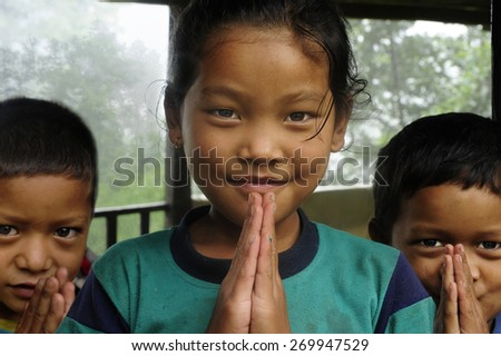 Ghorepani, Nepal - AUGUST 28, 2010: Nepali girl with her brothers saluting the photographer from his home in Ghorepani