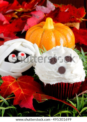 Ghost cupcakes for Halloween includes fondant wrapped mummy and cream cheese frosted ghoul with chocolate chip eyes, all edible