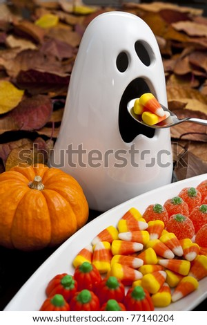 Ghost eating candy corns with a spoon surrounded by colorful fall leaves and Halloween candy - stock photo