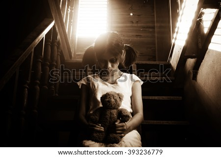 Ghost girl in haunted house holding teddy bear,Mysterious girl in white dress sitting on stairway in abandon house - stock photo