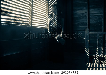 Ghost girl in haunted house,Mysterious girl in black dress standing in abandon house - stock photo