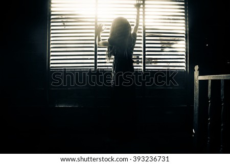 Ghost girl in haunted house,Mysterious girl in black dress standing in abandon house holding hand on the window  - stock photo
