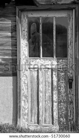 Ghost in an old farmhouse door  window, desaturated. - stock photo