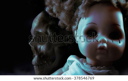 Ghost mystic doll. Scary horror plastic doll face with black tears and human skull on background. - stock photo