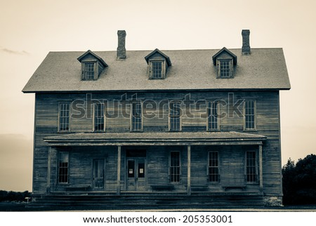 Ghost Of The Past. Century old abandoned opera house set against stormy gray skies.  Fayette State Historical Park.  Garden, Michigan   - stock photo