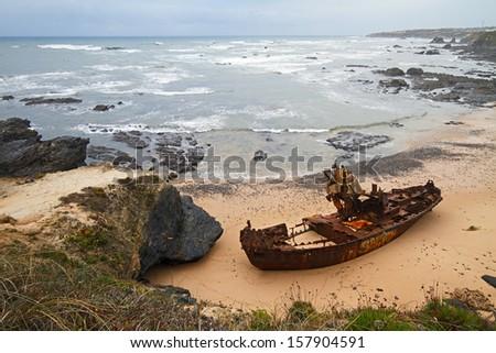 Ghost ship after shipwreck at beach of Vila Nova de Milfontes, Portugal. - stock photo