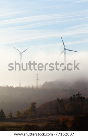 Ghostly shapes of large wind turbines dwarfing pylon of high-voltage transmission line on foggy morning in Eifel, rural Germany, Europe. - stock photo