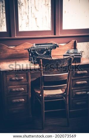 Ghostwriter Desk. Vintage Desk with Aged Typewriter and Wooden Ghostwriter Chair. - stock photo