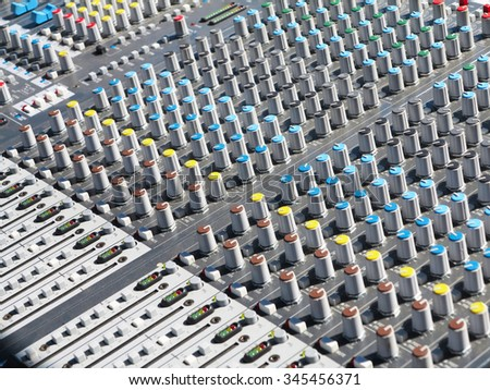 giant audio sound mixer console with color buttons and sliders - stock photo