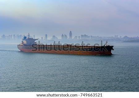 Giant bulk carrier vessel in ballast leaves the port of Qingdao along Jiaozhou Bay shore in the morning fog.