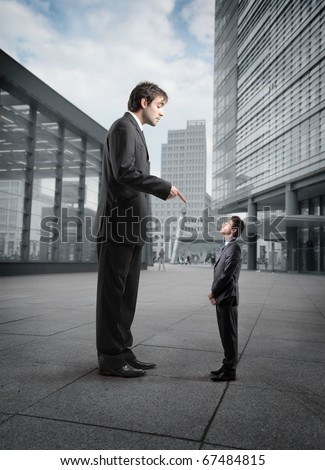 Giant businessman scolding a smaller one - stock photo