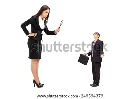 Giant businesswoman observing a tiny businessman through a magnifying glass isolated on white background - stock photo