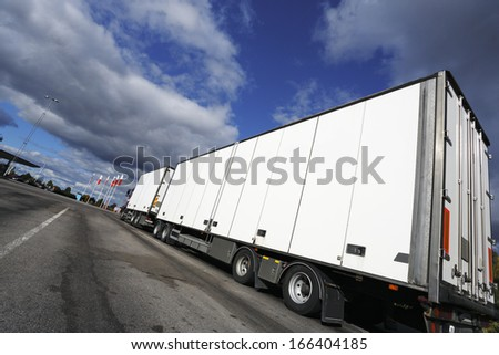 giant clean white truck, super wide angle view against blue sky.