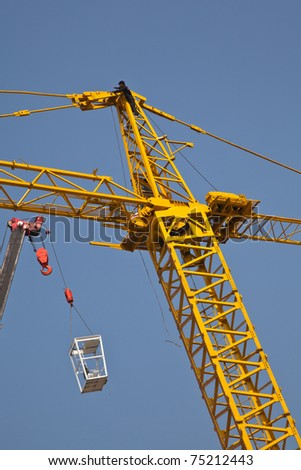 Giant crane lifting control cage onto the top. - stock photo