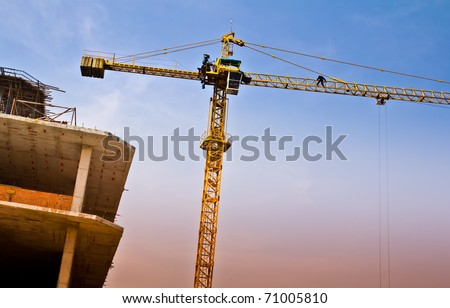Giant crane lifting structure engineer onto the building early in the morning. - stock photo