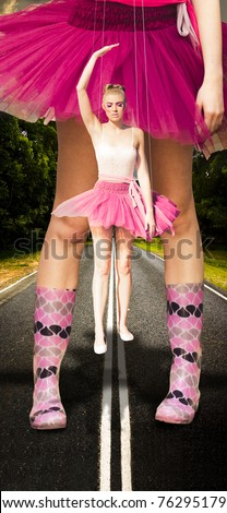 Giant Dancing Ballerina Woman Holds Herself As A Dance Puppet On Strings When Standing On A Road With Gigantic Wellington Boots In A Dancing In The Rain Concept - stock photo