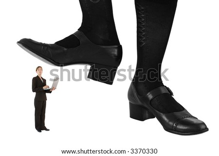 Giant feet preparing to crush a female business professional wearing tailored suit and holding a laptop computer. Conceptual image isolated on a white background. - stock photo