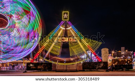 Giant Ferris Wheel and swing boat amusement ride side by side in night time shot with long exposure. - stock photo