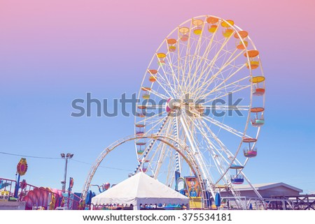 Giant ferris wheel in Amusement park with blue sky background pastel color tone