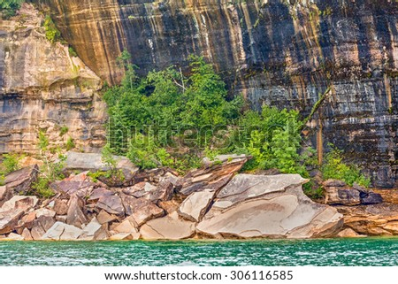Giant fractured rocks line the Lake Superior coast beneath giant sandstone cliffs at Upper Peninsula Michigan's Pictured Rocks National Lakeshore. - stock photo
